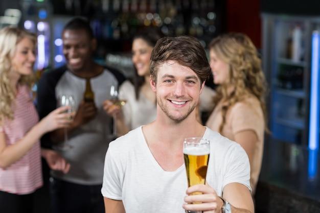 Uomo sorridente che mostra una birra con i suoi amici