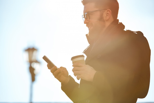 Uomo sorridente che per mezzo del telefono cellulare e bevendo caffè all'aperto