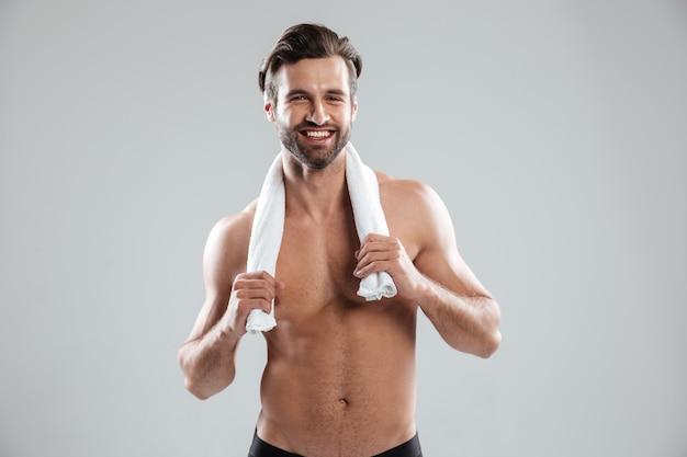 Uomo sorridente che posa con l'asciugamano alla macchina fotografica