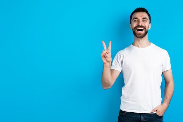Uomo sorridente che posa mentre facendo il segno di pace