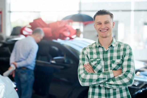 Uomo sorridente che posa vicino all'automobile con le armi attraversate.