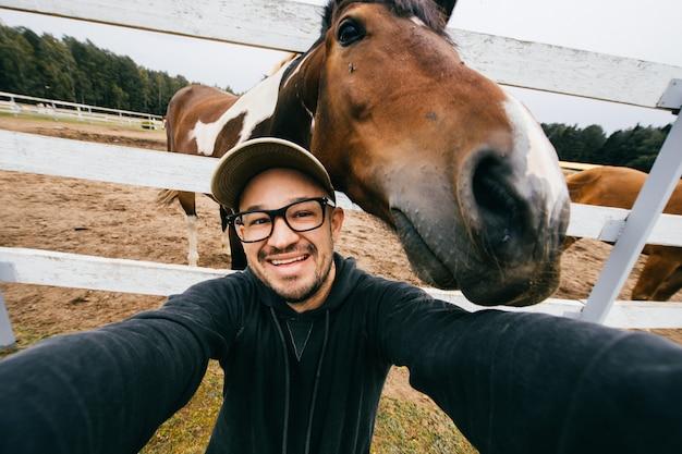 Uomo sorridente che prende selfie con la museruola del cavallo dietro lui