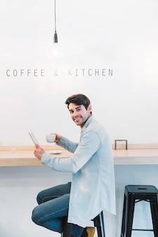 Uomo sorridente che si siede con la tazza e la compressa