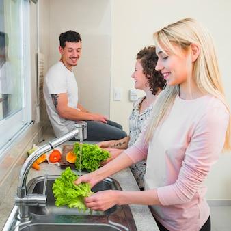 Uomo sorridente che si siede sul worktop della cucina che esamina due donne che puliscono la lattuga