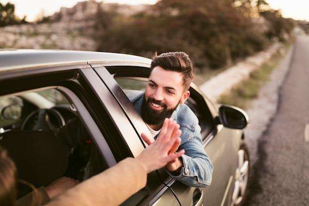 Uomo sorridente che si tiene per mano con la sua amica fuori dell'automobile