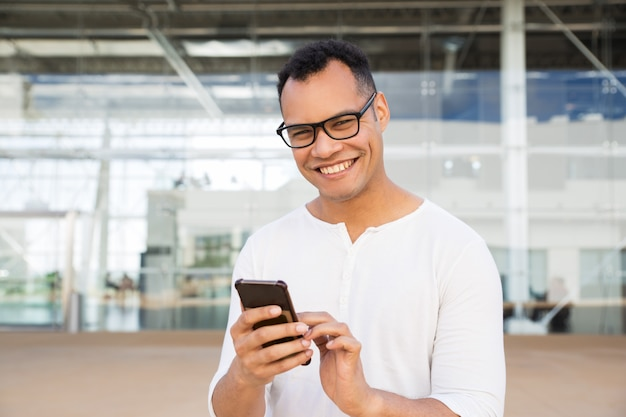 Uomo sorridente che sta all'edificio per uffici, tenente telefono in mani