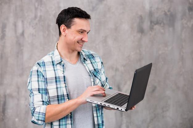 Uomo sorridente che sta e che per mezzo del computer portatile