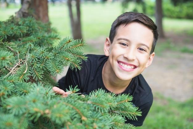 Uomo sorridente che sta vicino ai rami verdi dell'abete rosso dell'albero