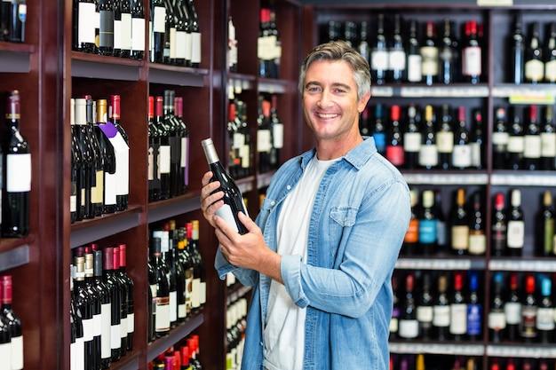 Uomo sorridente che tiene bottiglia di vino