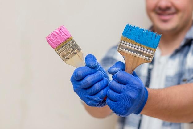 Uomo sorridente che tiene il pennello rosa e blu