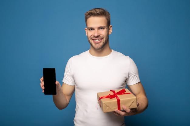 Uomo sorridente che tiene smartphone e contenitore di regalo isolato sul blu
