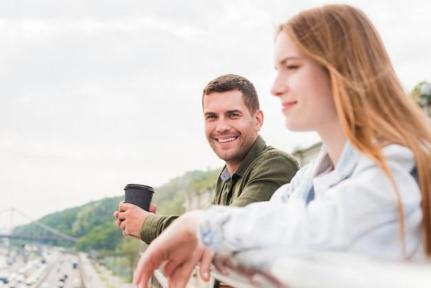 Uomo sorridente che tiene tazza monouso guardando la sua ragazza