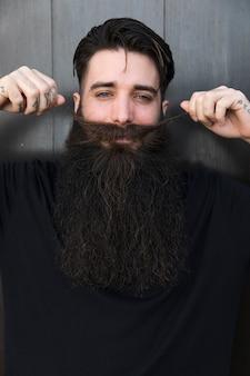 Uomo sorridente che tira i suoi baffi