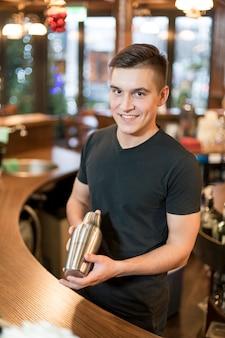 Uomo sorridente con agitatore per cocktail