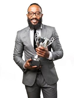 Uomo sorridente con il vestito e il trofeo