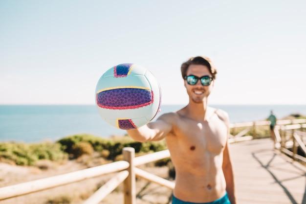 Uomo sorridente con pallavolo in spiaggia