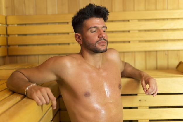 Uomo sorridente con un bagno di sauna in un bagno turco