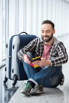 Uomo sorridente con una valigia e un passaporto pronti a viaggiare.