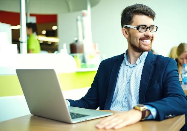 Uomo sorridente dei pantaloni a vita bassa di giovane modo nel caffè della città durante l'ora di pranzo con il taccuino in vestito