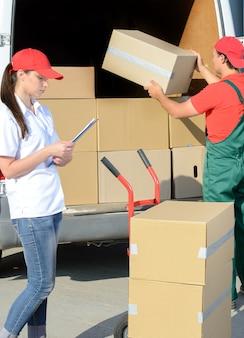 Uomo sorridente del corriere di consegna postale della donna e del giovane.