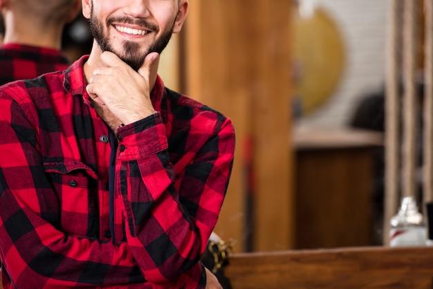 Uomo sorridente del primo piano con la barba dei pantaloni a vita bassa