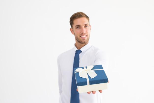 Uomo sorridente di affari che dà il contenitore di regalo con il nastro