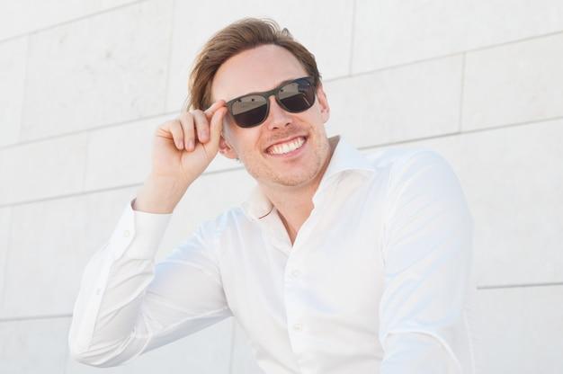 Uomo sorridente di affari che regola gli occhiali da sole all'aperto