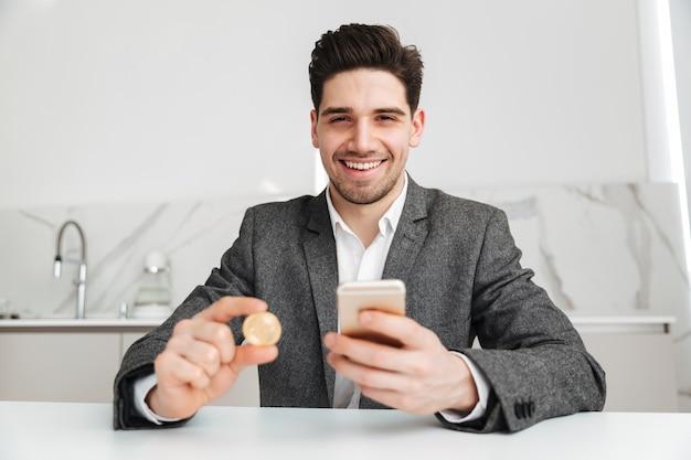 Uomo sorridente di affari che si siede dalla tabella e