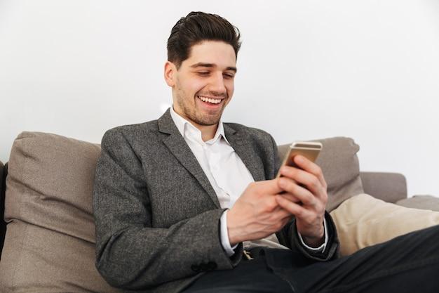 Uomo sorridente di affari che si siede sul sofà a casa