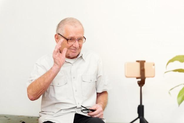 Uomo sorridente di eldery che esamina macchina fotografica che fa il video blog o chiamata a casa che si siede sul sofà che risale ritratto in linea di colpo in testa
