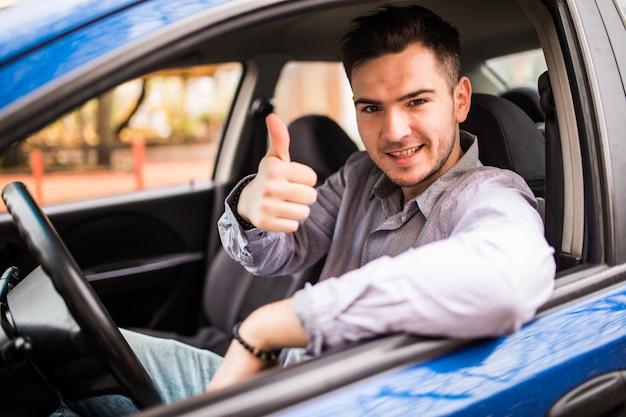 Uomo sorridente felice che si siede dentro l'automobile che mostra i pollici in su. bel ragazzo entusiasta del suo nuovo veicolo. espressione del viso positivo