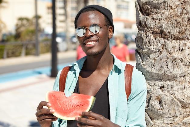 Uomo sorridente felice con lo zaino in piedi nel contesto urbano