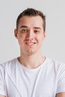 Uomo sorridente in maglietta bianca su sfondo grigio