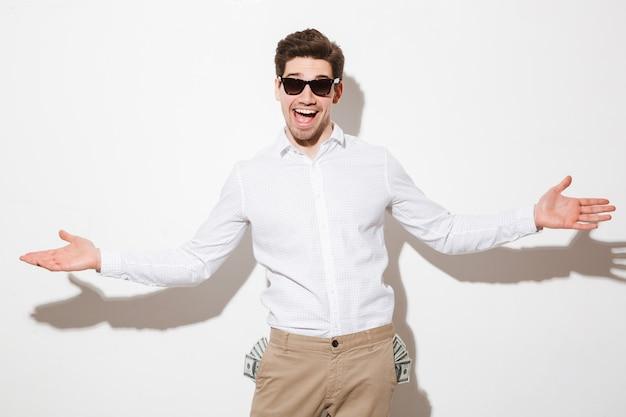 Uomo sorridente in occhiali da sole neri, alzando le mani in fortuna con un sacco di soldi denaro contante che sporge dalle tasche, isolato su uno spazio bianco con ombra