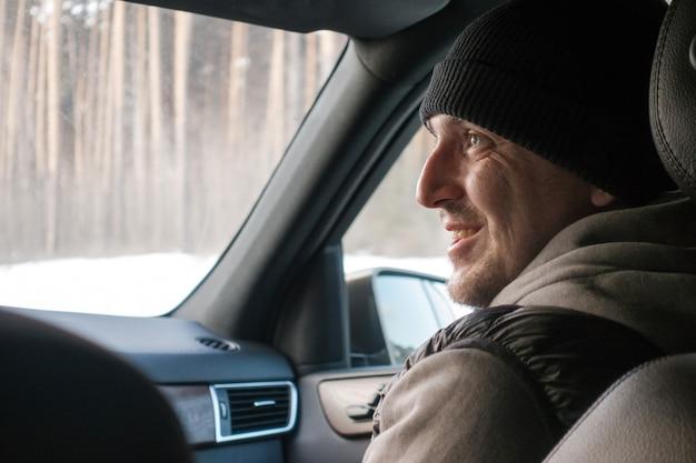 Uomo sorridente in outwear all'interno della macchina