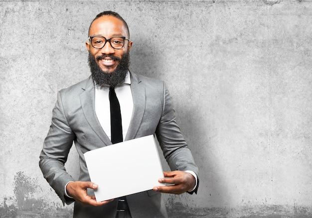 Uomo sorridente in vestito con una scatola bianca