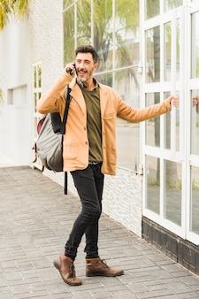 Uomo sorridente moderno con il suo zaino parlando sul cellulare mentre si apre la porta a vetri