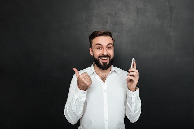 Uomo sorridente soddisfatto in camicia bianca che tiene smartphone e che gesturing pollice da parte sopra grigio scuro