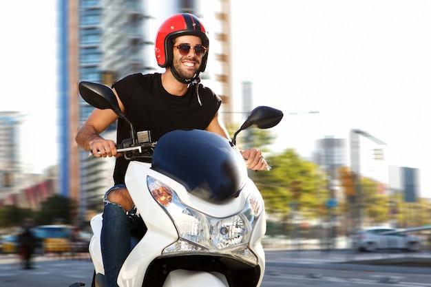 Uomo sorridente su giro in moto sulla strada della città