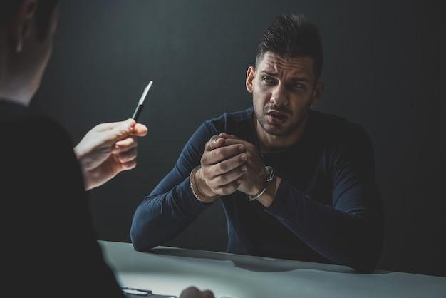 Uomo sospetto o criminale con manette nella stanza degli interrogatori