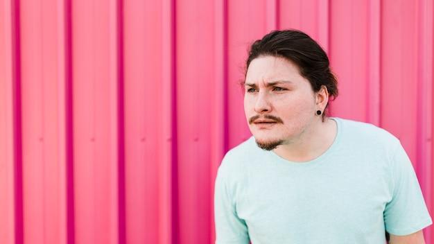 Uomo sospettoso che sta contro la lamina di metallo ondulata rosa