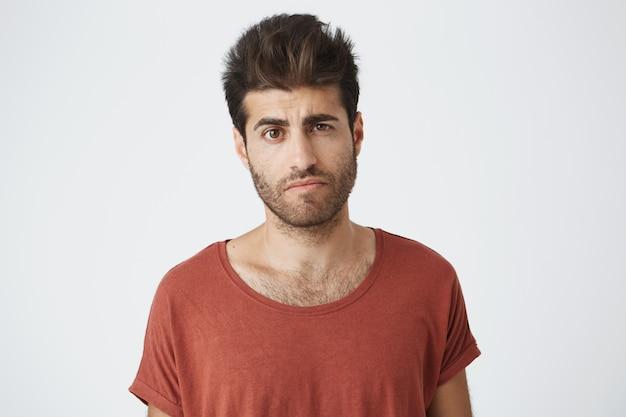 Uomo spagnolo dall'aspetto scettico in maglietta rossa con acconciatura alla moda e barba con espressione sospetta e incerta, ascoltando la storia della sua ragazza della scorsa notte.