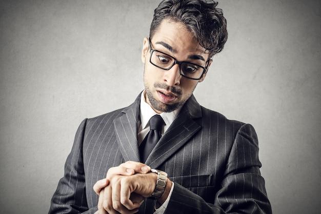 Uomo spaventato guardando orologio