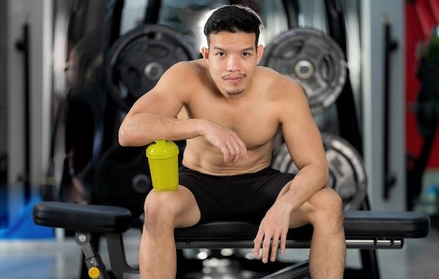 Uomo sportivo allenamento con manubri in palestra