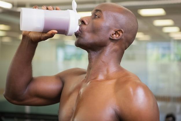 Uomo sportivo che beve proteina in palestra