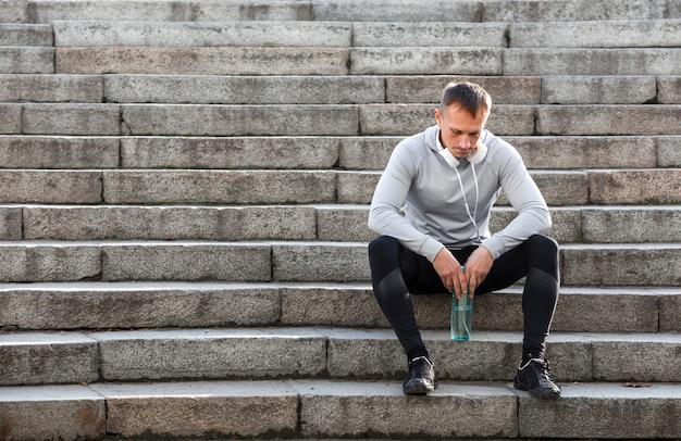 Uomo sportivo che riposa sulle scale