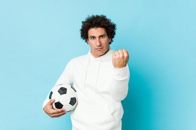 Uomo sportivo che tiene un pallone da calcio che mostra pugno alla macchina fotografica, espressione facciale aggressiva.