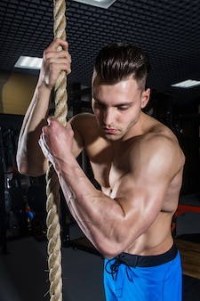 Uomo sportivo con grandi muscoli che si allenano in palestra, fitness e pressa addominale pompata
