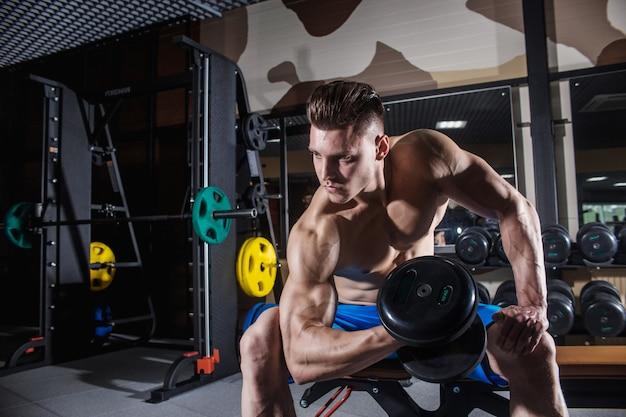 Uomo sportivo con grandi muscoli e un'ampia schiena si allena in palestra