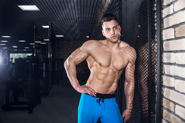 Uomo sportivo con grandi muscoli in palestra, fitness e pressa addominale pompata
